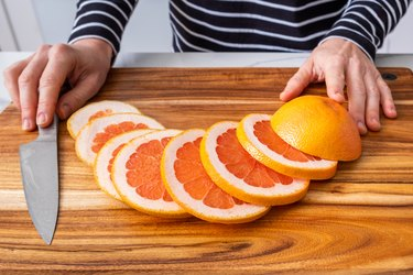 Caucasian woman hands placed on wooden chopping board with sliced red grapefruit and knife