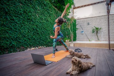 Woman doing a live-streaming workout on her deck with her dogs