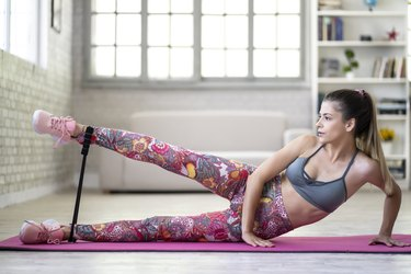 Woman practicing at home, using resistance band