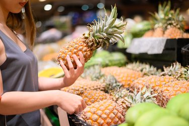 Young woman picking up fresh pineapple at grocery store or supermarket