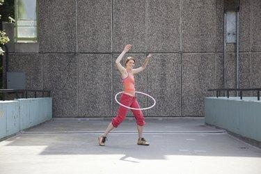 Woman hula hooping on city street