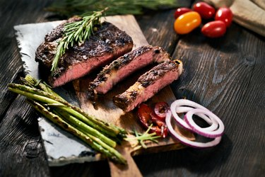 sliced steak with asparagus and red onion on wooden cutting board
