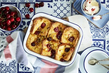 Cherry bread and butter pudding on blue and white table with cherries