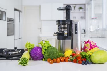Juicer with various fruits and vegetables in kitchen