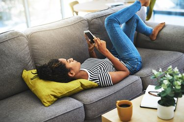Woman looking at her phone on the couch