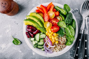 Healthy vegan lunch features immune boosting foods like avocado, quinoa, tomato, cucumber, red beans, spinach, red onion and red paprika vegetables salad.