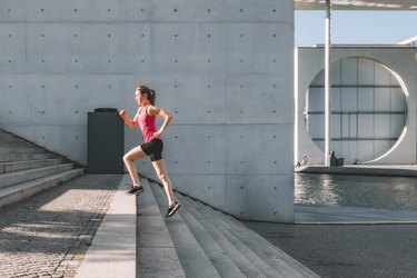 sports woman running up stairs outdoors