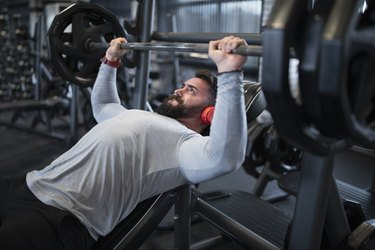 Man Doing the Bench Press In Gym as Part of an Upper-Body Superset
