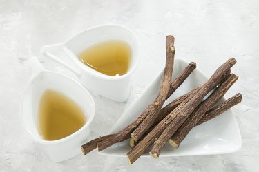 Licorice tea and roots on white background
