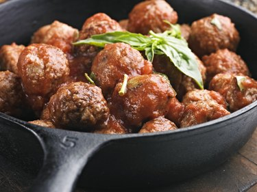 A cast iron pan full of meatballs in tomato sauce