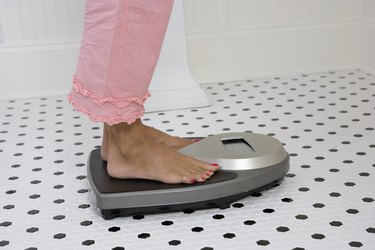 Woman on the flat belly diet weighing herself on a bathroom scale