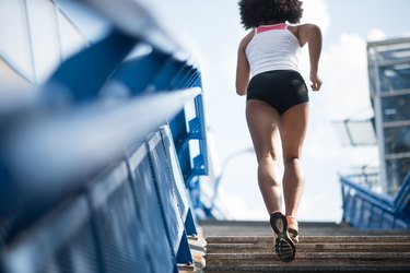 Sporty woman running upstairs - fitness concept