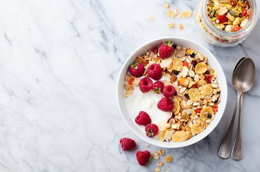 Healthy breakfast. Fresh granola, muesli, yogurt, berries on marble background. Top view. Copy space