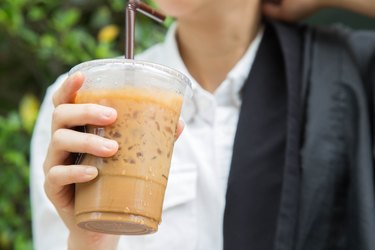a man drinking iced coffee