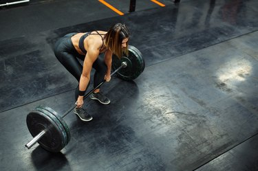 Woman performs deadlift with weight at the gym