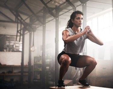 woman squating in gym doing quick plyometric workout