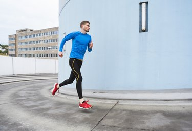 Young man doing a HIIT running workout in the city