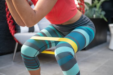 woman exercising at home with resistance band doing hip strengthening exercises