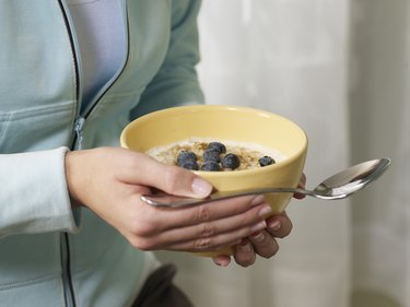 Woman holding bowl of oatmeal with blueberries