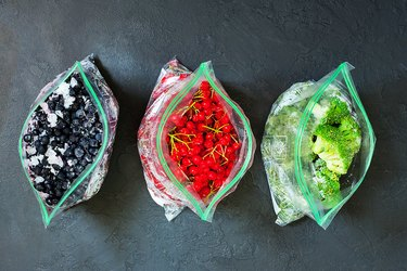 Frozen berries and vegetables in bags in packages on dark concrete background - close up