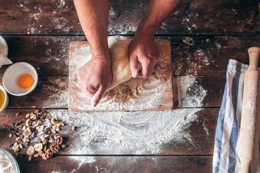 Hands kneading raw dough on table flat lay