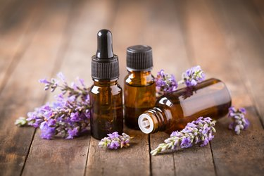 Three bottles of lavender essential oil with dried lavender on a wooden table