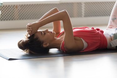 Calm woman lying on mat relaxing after training at home
