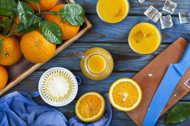 Orange juice in a glass, whole oranges, and sliced oranges on a blue wooden table.