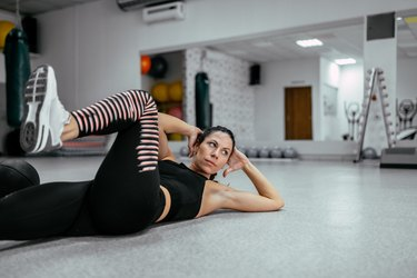 Young sporty woman doing bicycle crunches. Abs workout.