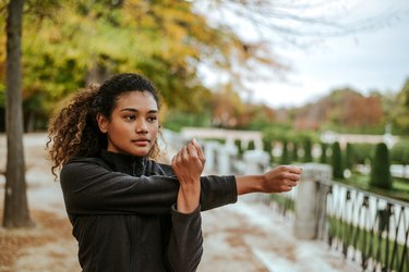 Beautiful young woman doing stretching exercises while standing outdoors.