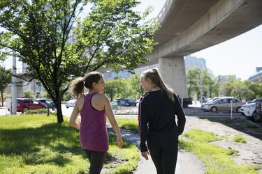 Women talking and walking on sunny, urban path