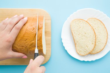 Woman's hands cutting loaf of white bread with knife. Slices on plate on pastel blue desk. Preparing breakfast. Point of view shot. Closeup. Top view.