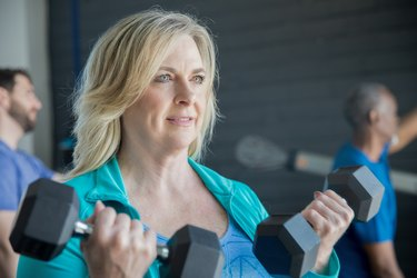Mature woman smiling while lifting weights in busy gym