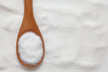 Wooden spoonful of white sugar just scooped up