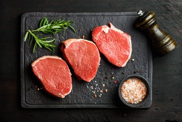 Raw Round steaks with spices and rosemary