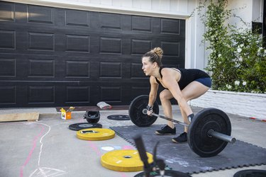 Woman doing deadlifts in front of her garage.