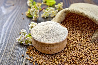 Flour buckwheat in bowl with cereals and flower on board