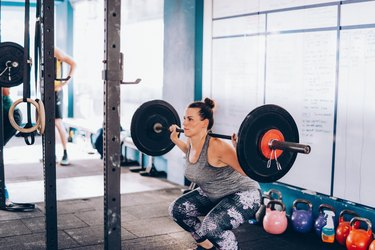 Cross training in Asia - woman crouching with weights