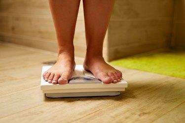 Female feet on weight scale in a bathroom