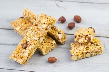 Homemade protein bars with roasted nuts, selective focus, wooden background