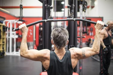 Rear view of elderly man doing Lat Pull Down exercise on gym equipment