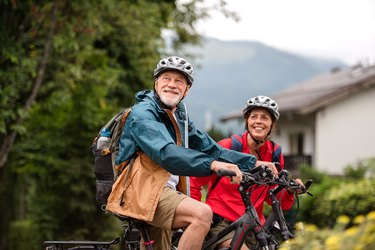 Senior couple tourist with bicycles cycling in town on holiday.