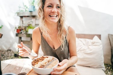 older woman smiling and eating a healthy breakfast bowl