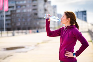 Female athlete drinking a water bottle after a workout