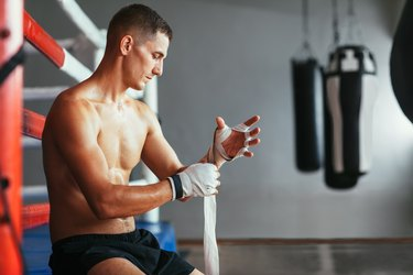 Male boxer is wrapping hands with boxing wraps