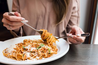 girl eating starchy spaghetti Bolognese, winding it around a fork with a spoon.