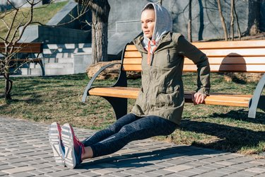Slim young woman in sportswear and hood