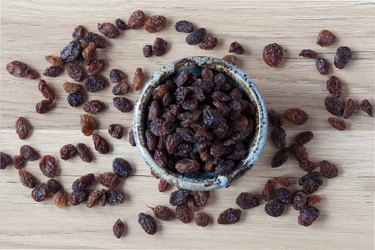 Organic raisins in bowl on wood