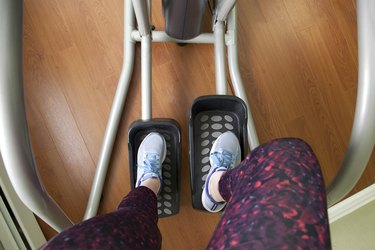 Sneakers and workout clothes on legs using the elliptical