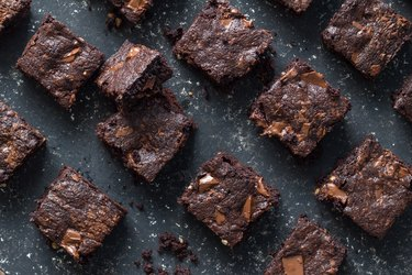 Baked chocolate brownie squares on mottled grey background texture - selective focus